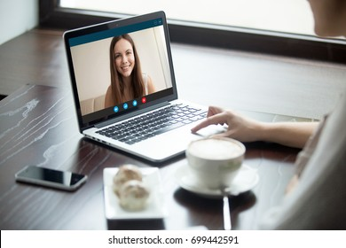 Woman making video call to girlfriend in cafe, communicating via app on laptop with close foreign best long distance friend, talking by web camera, using virtual chat, focus on screen, close up view