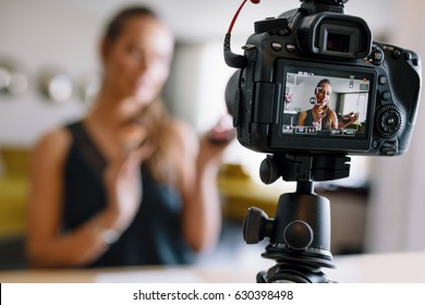 Woman making a video for her blog on cosmetics using a tripod mounted digital camera. Young female blogger on camera screen holding cosmetics.