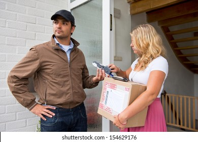 Woman making a wireless payment to a delivery guy for a cash on delivery parcel. She types her pin code on the cash machine, whilst the postal worker looks away
