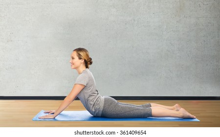 woman making yoga in dog pose on mat