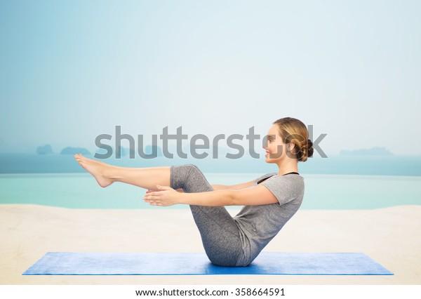 woman making yoga in half-boat pose on mat
