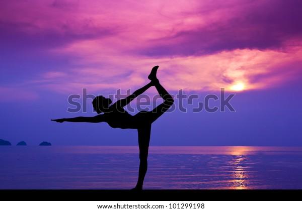 Woman making yoga on the beach