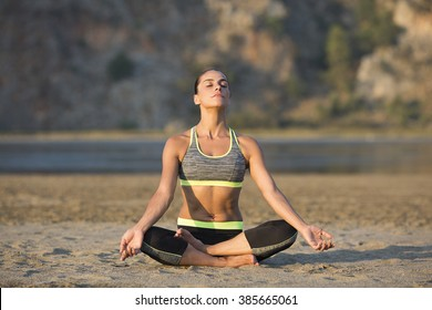 Woman making yoga and pilates on sand