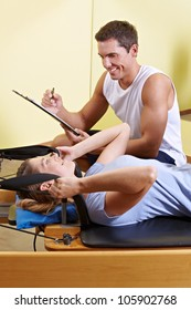 Woman and male trainer talking in fitness center while exercising