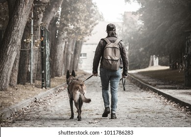 Woman with a malinois. Post apocalypse. travel on foot with your dog. Woman walking on a stone path with a backpack. Woman walking towards the building at the end of the road.