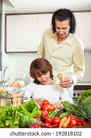Woman and man  adding spices or salt to the pot and in home kitchen