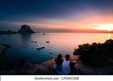Woman and man back to the front watching a beautiful sunset at the beach. The beach is called Es Vedra, in Ibiza and belongs to balearic islands, in Spain
