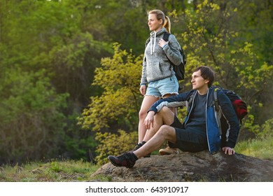 Woman and man with backpacks walking on the forest and mountain and enjoying the nature. Couple resting. Travel, vacation, holidays and adventure concept.