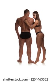 """Woman and man bodybuilders athletes in black bikini suits posing on a white background. Photo made in the style of """"low key""""."""