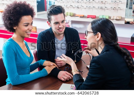 827e483116 Woman and man buying glasses at optician store getting advice from saleslady