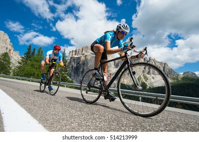 woman and man by road cycling downhill in the dolomites