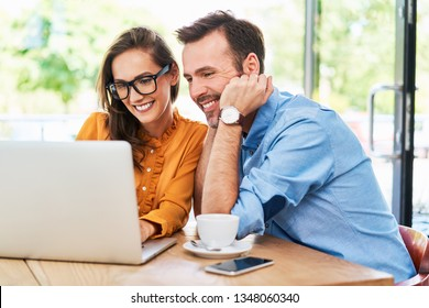 Woman and man at cafe using laptop. Couple spending time at cafeteria browsing internet on computer