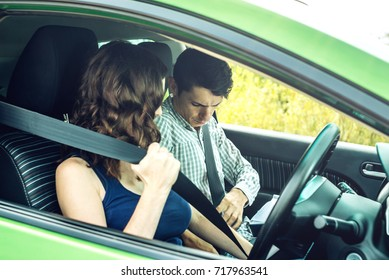The woman and the man in the car wear a seat belt. The concept of road safety and observance of traffic rules