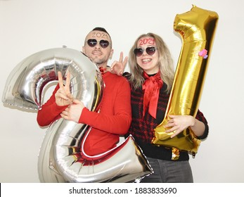 woman and man celebrtaing new year 2021 or silvester 2020 at home quarantine. lockdown. coronavirus crisis. boy and girl holding big nubmer ballons and have 2021 written on foreheads. twenty one.