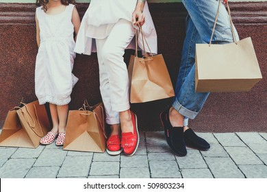 Woman, man and child with shopping bags near the shopping center. Stylish family on sale. Concept of total purchases, style and fashion. Family on the shopping
