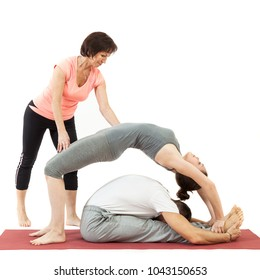 woman and man doing yoga under the guidance of a trainer