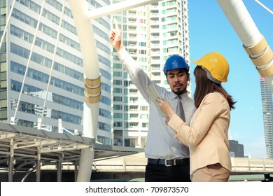 Woman and man engineer are work  on the site construction in city view background