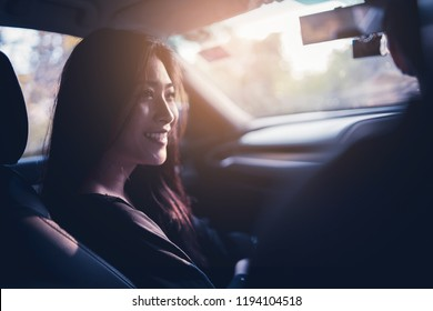 woman and man Enjoying to travel. Asian couple sitting on the front passenger seats ,she smiling while  driving a car  on the road