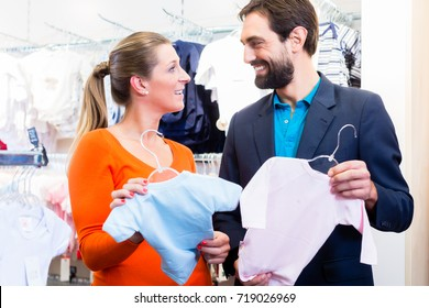 Woman and man expecting twins buying baby clothes, holding pink and blue suits for girl and boy