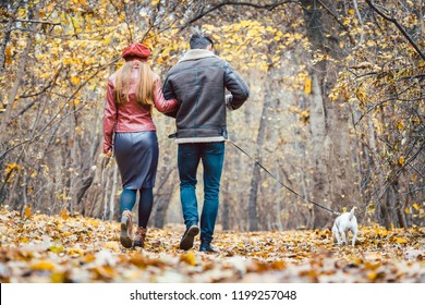 Woman and man in the fall strolling with their dog in the park embracing each other in love
