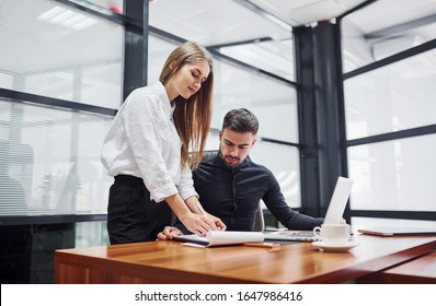 Woman and man in formal clothes working together indoors in the office by table. - Shutterstock ID 1647986416