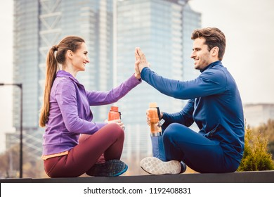 Woman and man giving hi-five after fitness sport in a city, in the background a high-rise building is to be seen