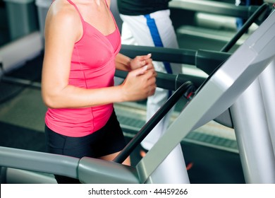 Woman and man in gym - only legs to be seen - exercising running on the treadmill to gain more fitness; motion blur in limbs for dynamic