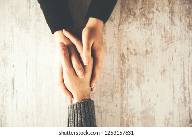woman and man hand on wooden table