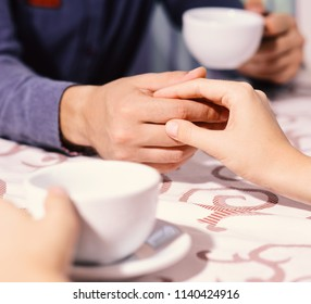 Woman and man have a date. Male and female hands on table, defocused. Rendezvous and coffee break concept. Couple in love holds cups of coffee at table.