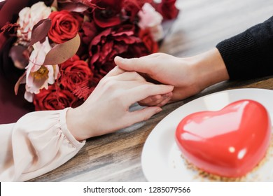 Woman and man hold hands close up. On the background of a table in a cafe. Bouquet and cake in the form of a heart on a background. St. Valentine's Day.