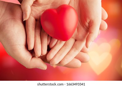 A woman and man hold a red heart in their hands.