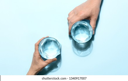Woman and man are holding glasses full of clear purified water, minimalist  concept, elevated view composition