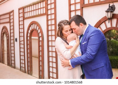 Woman and man holding a newborn. Mom, dad and baby.