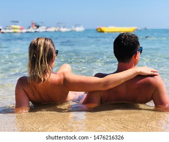 Woman and man hugging on the summer beach. Happy couple.