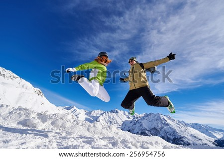 49bc720abd47 woman and a man in a jump in the mountains of Austria against the blue sky