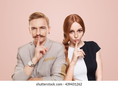 Woman and man keep secret. Couple shows hush sign, adultery, relationship issue, marriage cheating concept. Secret love, jealousy. Mystery, privacy, intimacy. Young beautiful couple isolated at pink