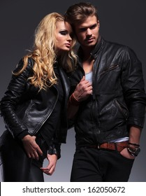 woman and man in leather clothes standing shoulder to shoulder and looking away