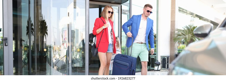 Woman and man leave the building with suitcase. Meeting services concept