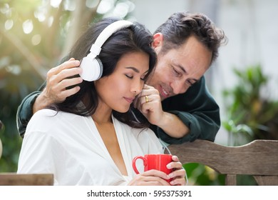 woman and man listening to music on headphones