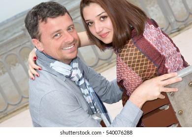 Woman and man looking at camera and cuddling