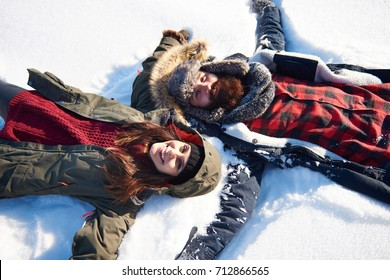 Woman and man making snow angel