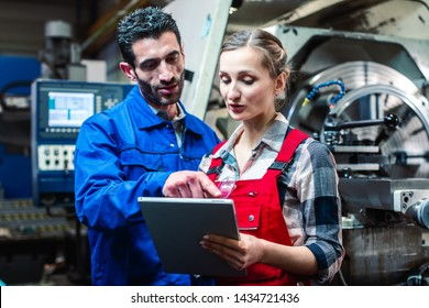 Woman and man manufacturing worker in discussion writing on tablet computer