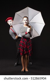 Woman and man mimes with white umbrella on isolated black background