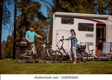 Woman with a man on electric bike resting at the campsite. Family vacation travel, holiday trip in motorhome RV, Caravan car Vacation.