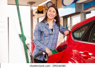 Woman man refuelling a car at a petrol station