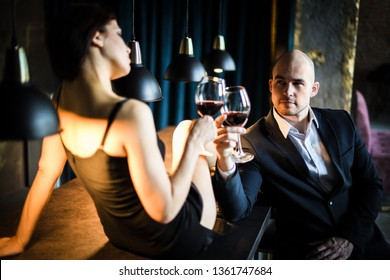 A woman and a man in a restaurant. A man in a black suit sitting at the bar, next to him sitting on the bar dark-haired girl in a black dress, they are minted glasses of red wine.