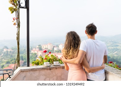 Woman and man romantic couple on terrace garden outside in Italy with mountain view of Chiusi cityscape Umbria near Tuscany and tea or coffee cups in breakfast morning with fog mist