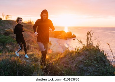 woman and man running on beach. Fit young fitness couple exercising during sunrise or sunset