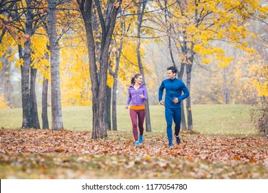 Woman and man running on a path in autumn park for sport