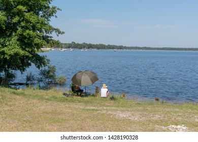 woman and man seated next to the lake fishing and relaxing in Lacanau France